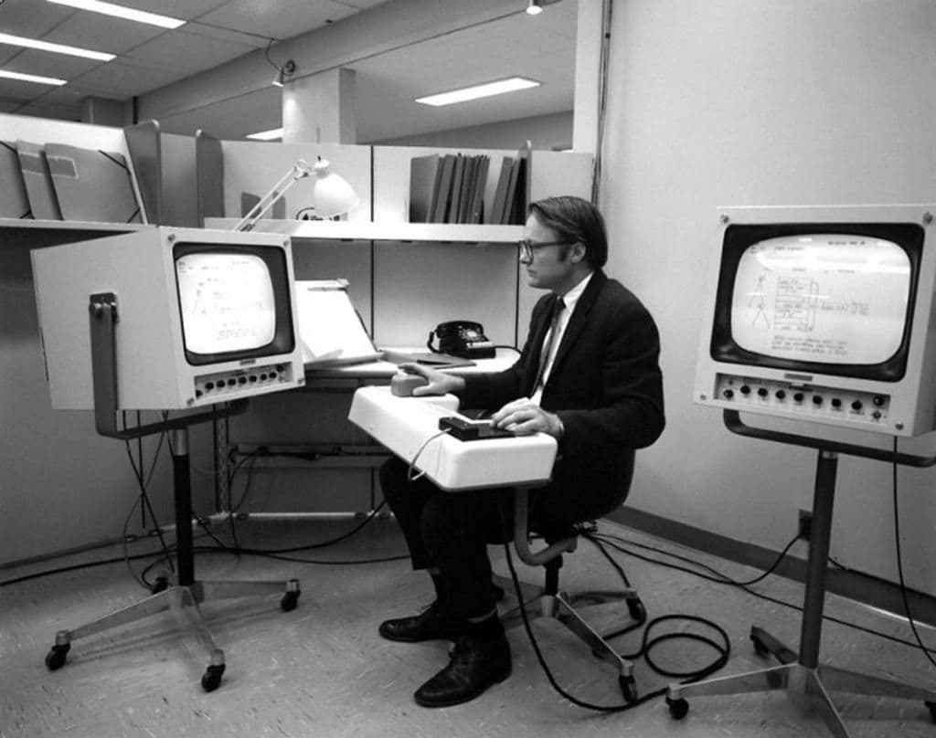 Bill English in 1968, sitting in an office between two CRT monitors, with a large keyboard and early computer mouse on his lap.